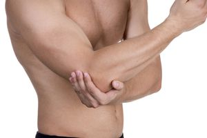 Photo of a man holding his elbow.
