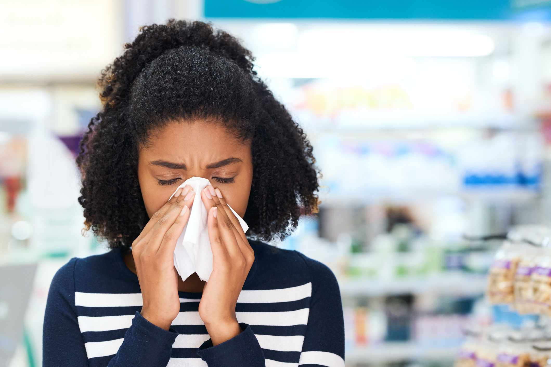 Young woman blowing her nose in a pharmacy