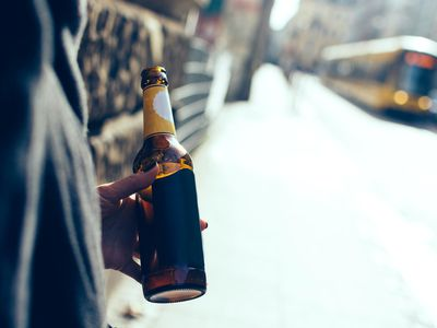Person holding bottle of beer