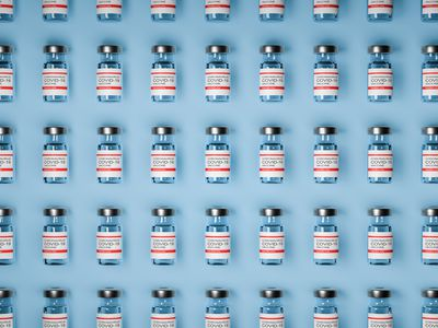 A bunch of COVID vaccine ampules neatly lined up on a blue background.