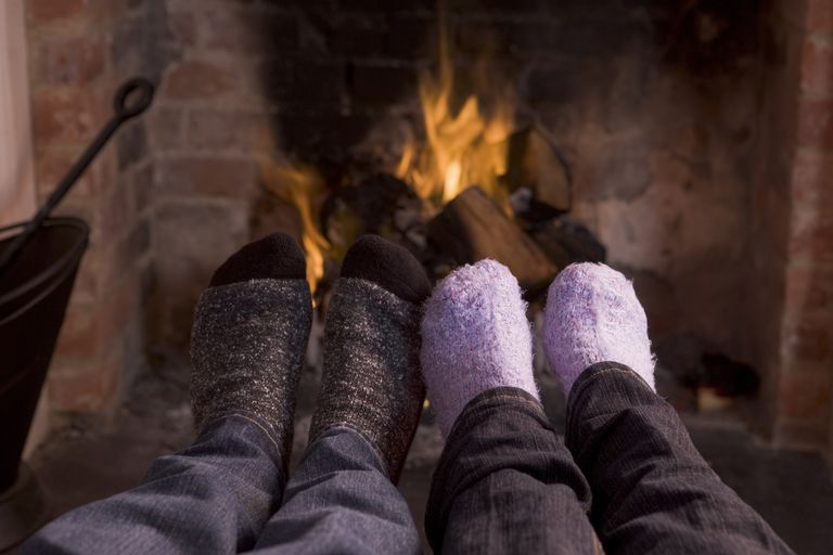 Couple's feet warming at a fireplace
