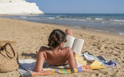 a woman sunbathing and reading on the beach
