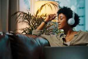 BIPOC woman listening to headphones in a dim room