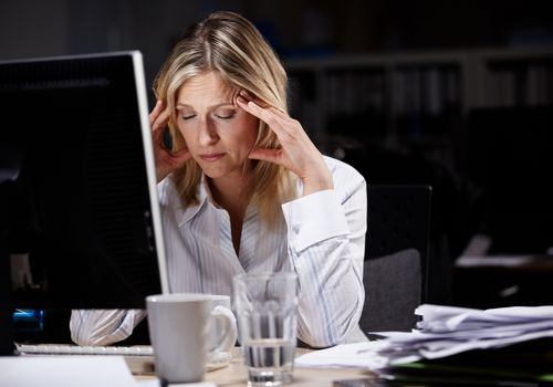 woman with headache working late in the office