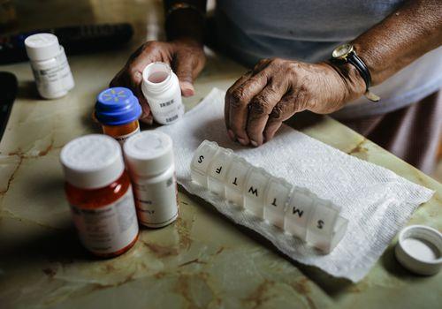 Older adult taking weekly medicine.