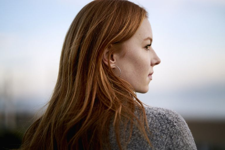 a woman with red hair facing away from the camera