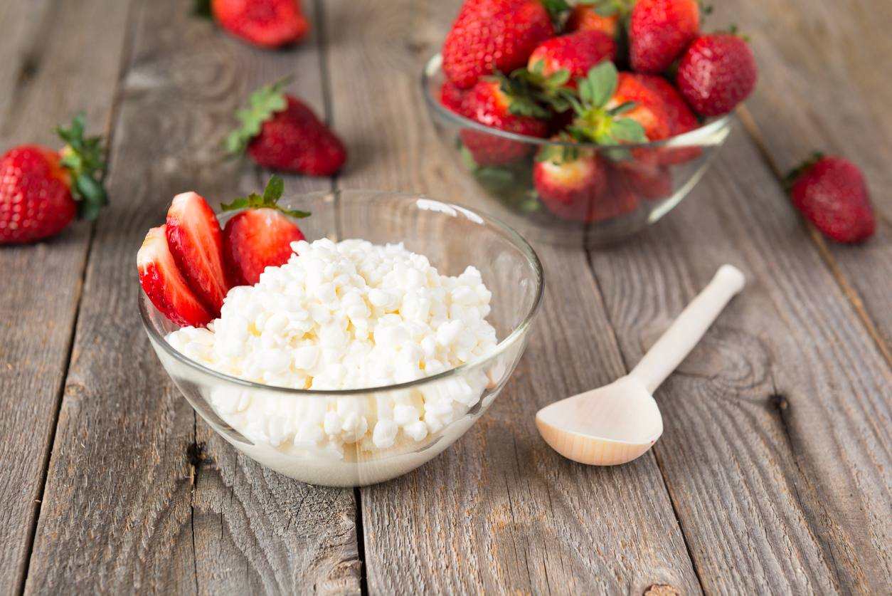 Bowl of cottage cheese with a side of strawberries