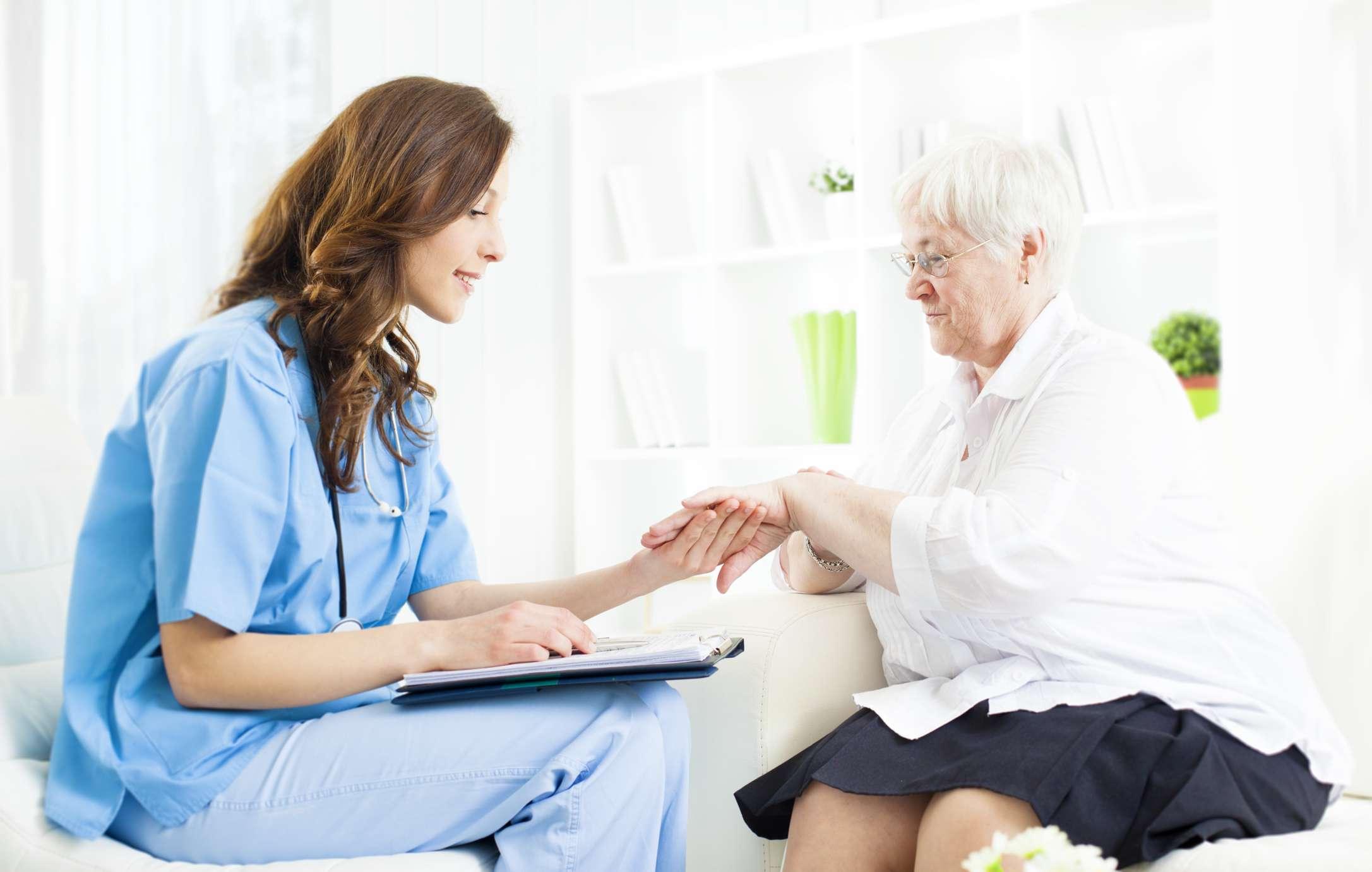 Nurse checking older woman's skin