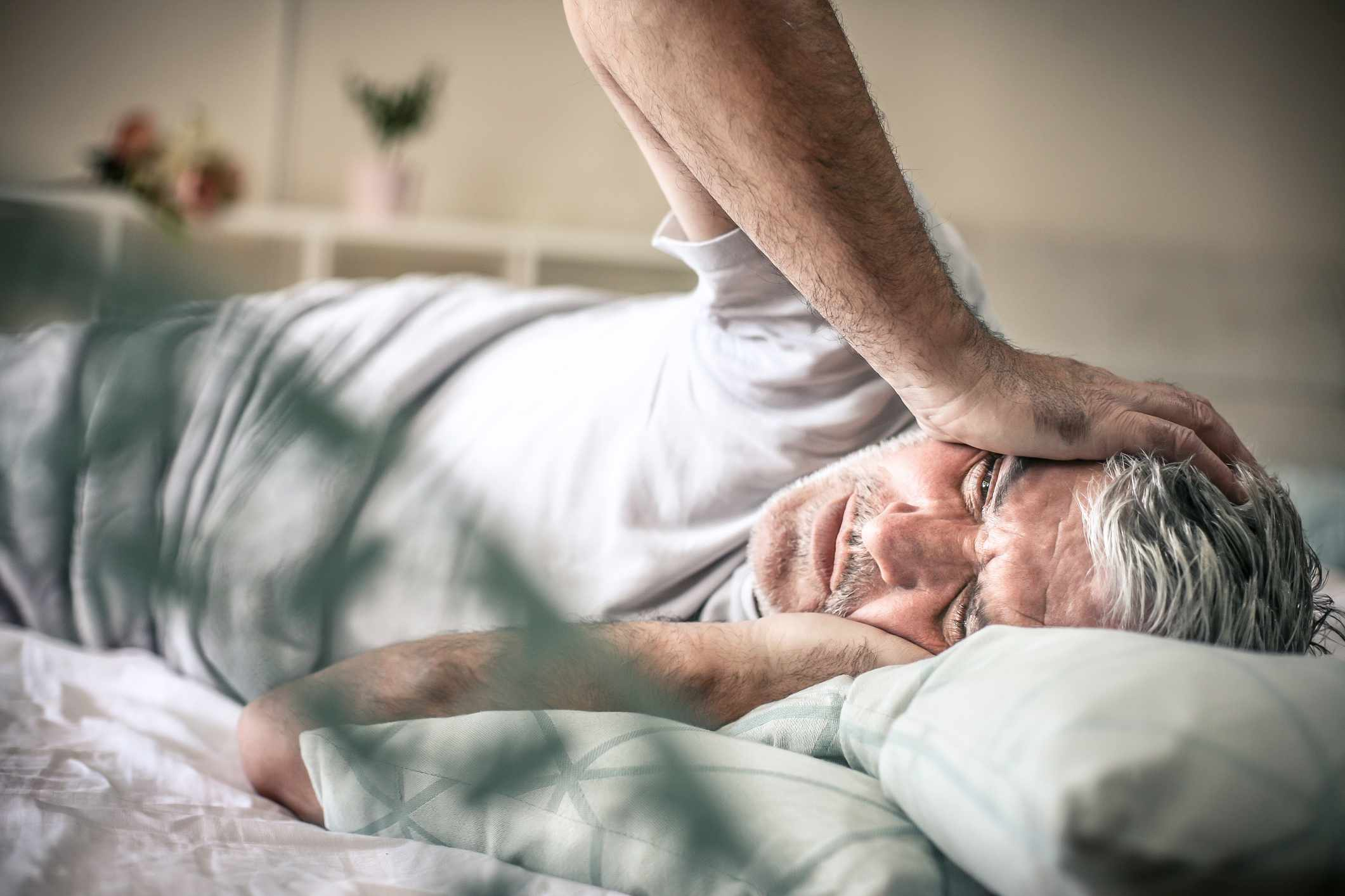 A man laying in bed with severe head pain
