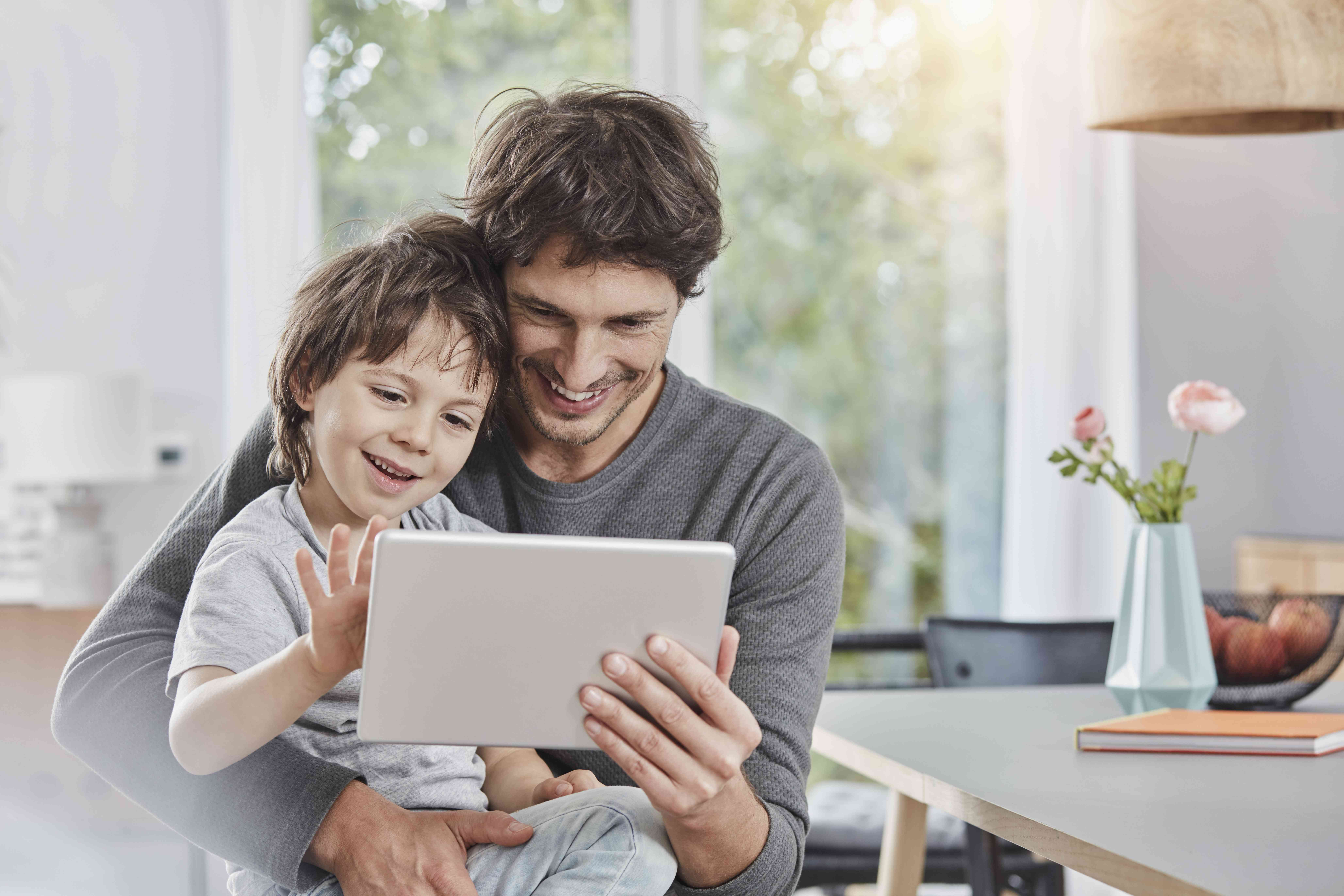 Father and son using an autism app on a tablet together