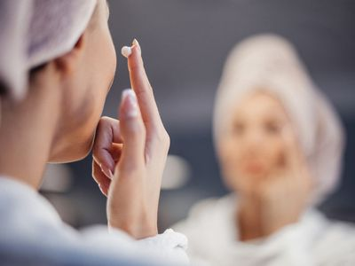 Young woman applying face cream.