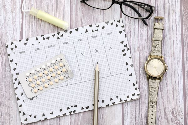 A calendar for tracking periods with a tampon and birth control pills.