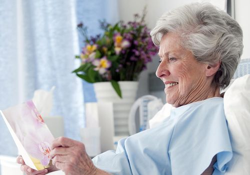 Senior woman reading card in hospital