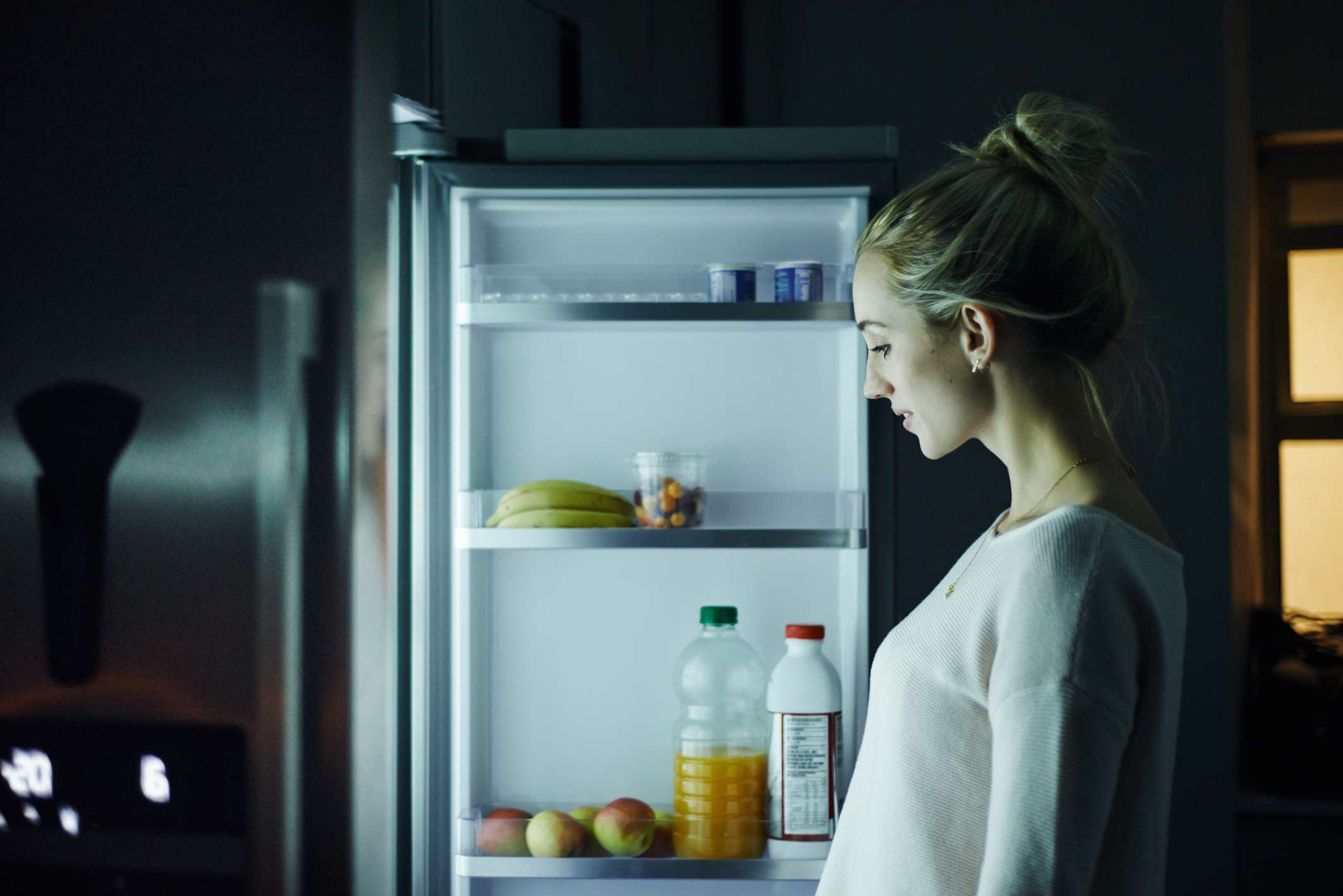 Shot of a young woman opening the fridge at night in her home