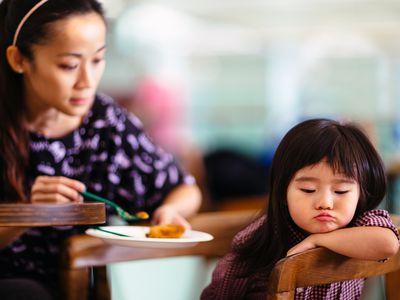 Toddler girl turning head away refusing to eat