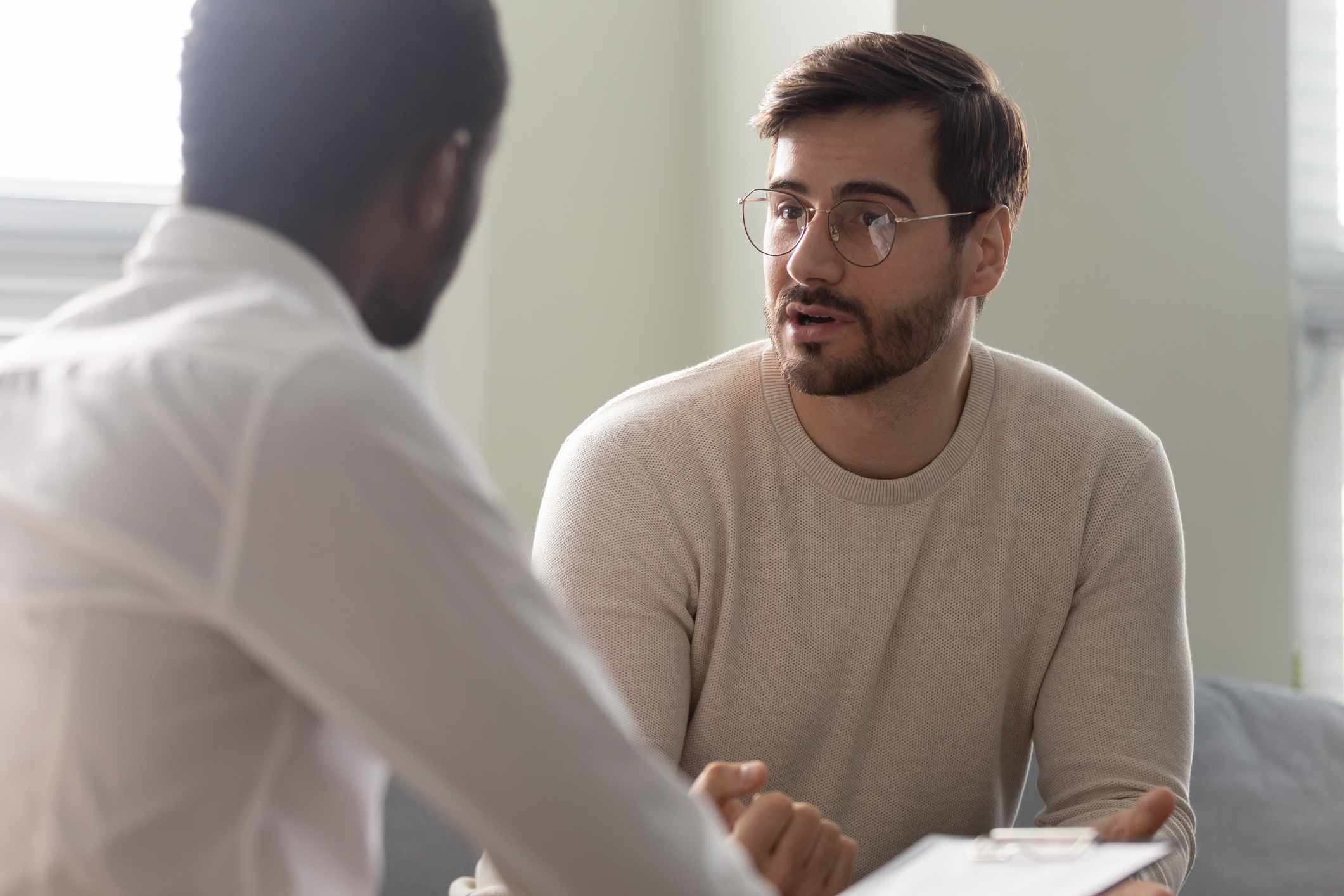 Psychologist holding clipboard with card sitting in front of patient listens his mental health complaints