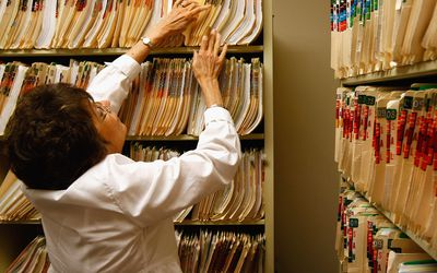 An office assistant retrieves medical records.