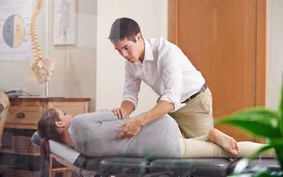 Chiropractor adjusting a woman's back in his office