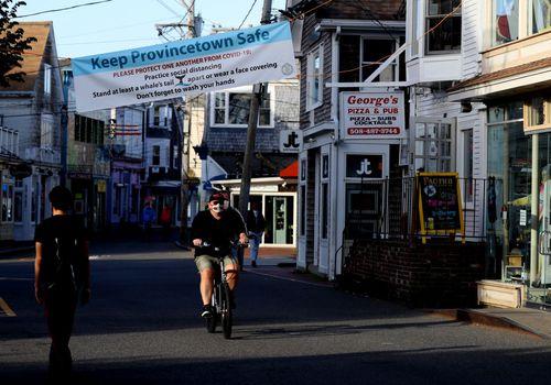 Man bikes through Provincetown under COVID banner