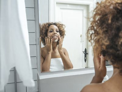 Young woman in bathroom applying face cream