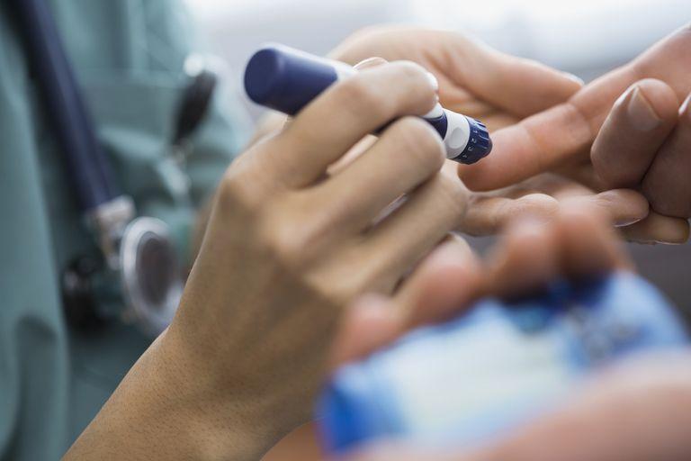 Nurse using insulin pen on patients finger