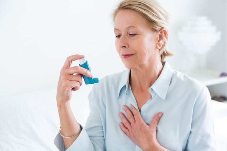 Woman using an aerosol inhaler that contains bronchodilator for the treatment of asthma, The inhaler dilates lungs airways to improve breathing.