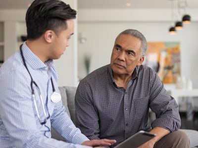 A doctor of Asian descent and an elderly patient are indoors at the man's home. The doctor is talking to his patient about his depression and anxiety while showing him his tablet.