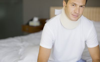 Man sitting on bed with neck brace