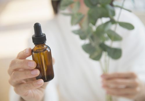 woman holding essential oil bottle