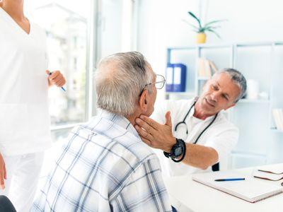 Doctor examining older man's lymph nodes
