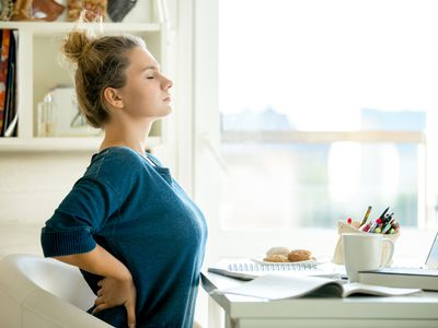 Portrait of an attractive woman at the table backache pose