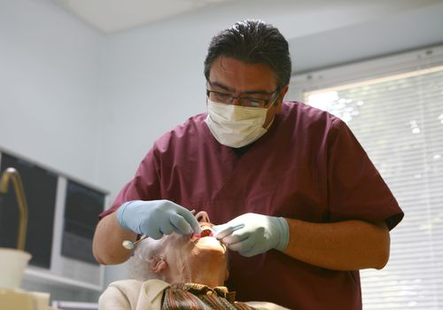 Dentist working on older woman