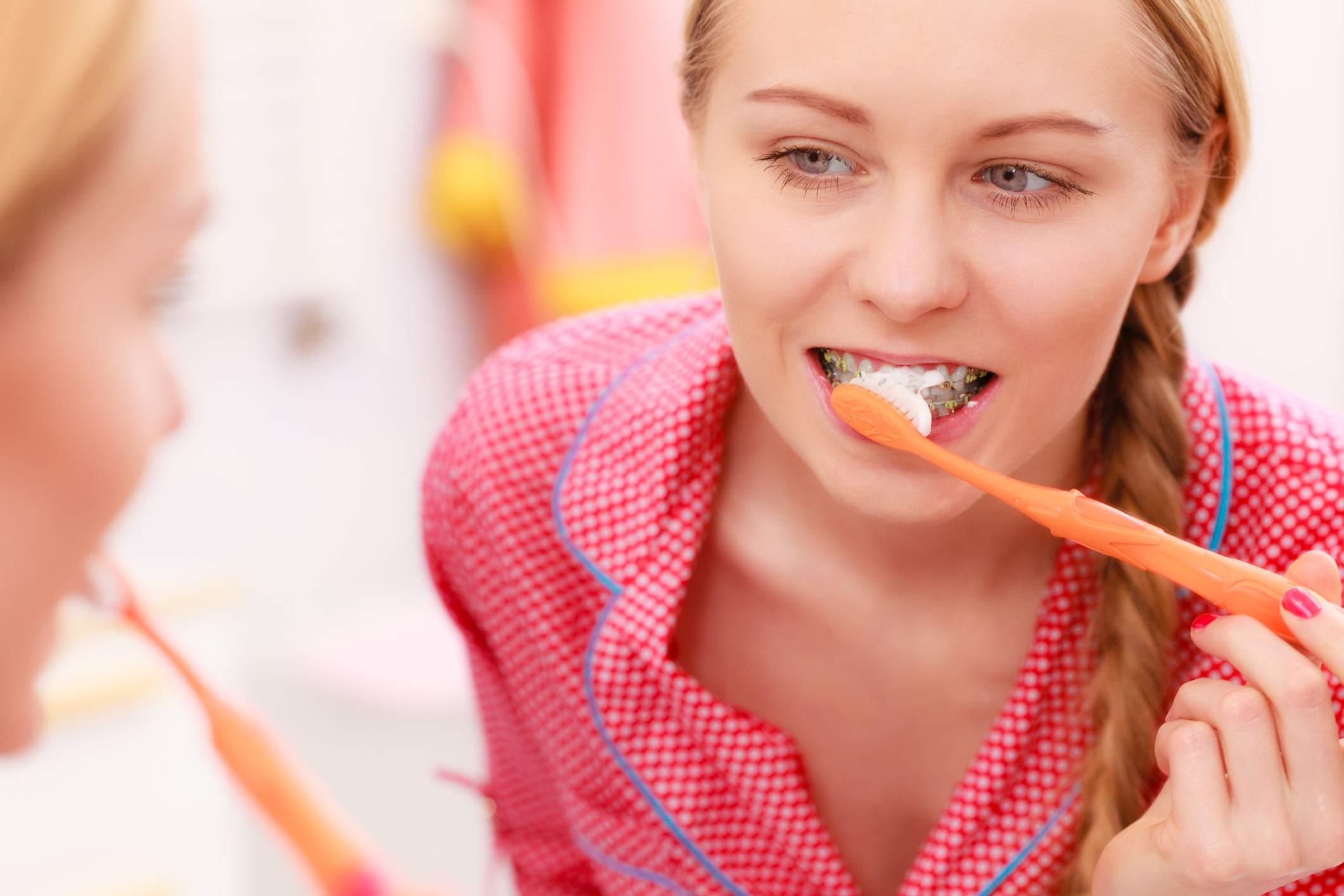 teen girl with braces brushing teeth