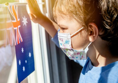 Young Australian boy holding flag and wearing mask