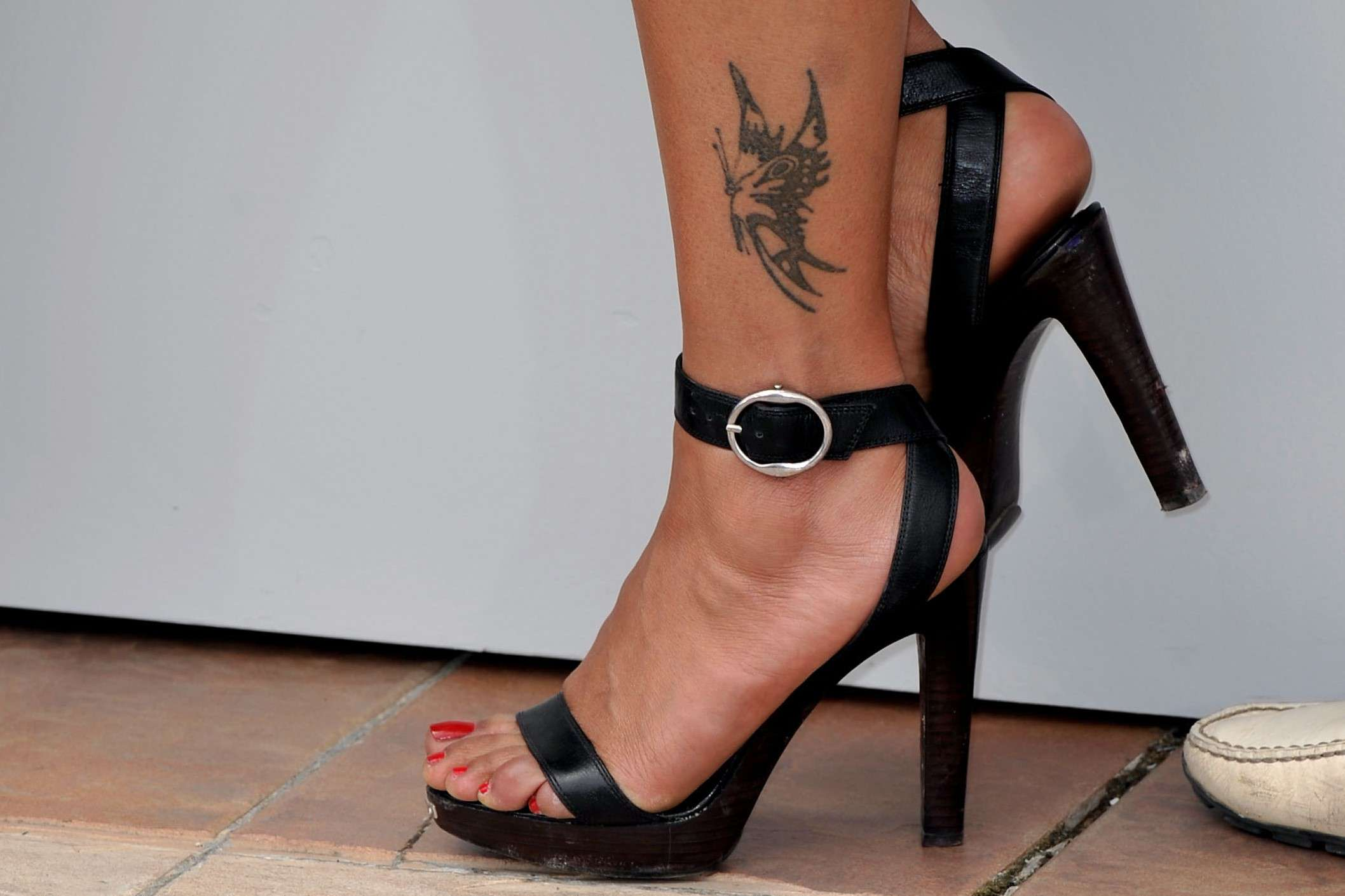 Woman wearing black high heeled sandals with a butterfly tattoo on her ankle