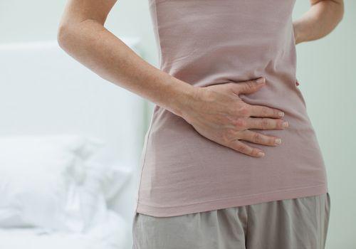 Woman rubbing aching stomach