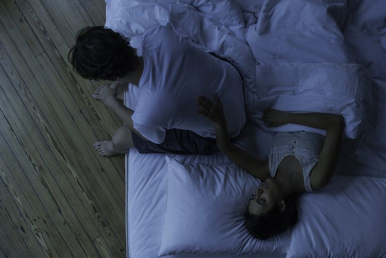 man sitting on edge of bed at night with woman touching his back