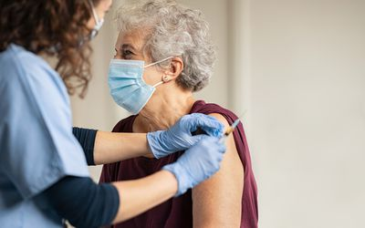 Older woman wearing a mask receiving a vaccine.
