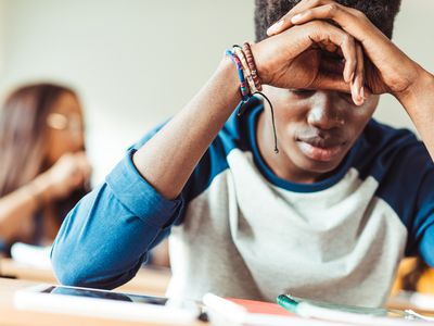 A young Black man in class appearing distraught.