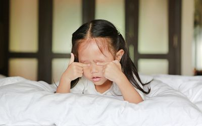 Toddler laying on bed rubbing her eyes