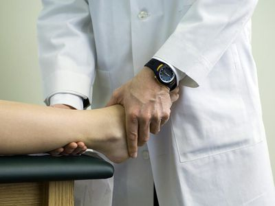 Doctor examining patient's foot and ankle