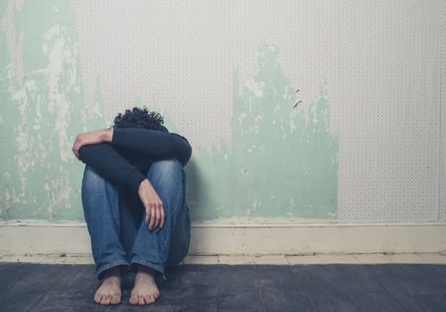 Depressed woman sitting on the ground with her head in her arms