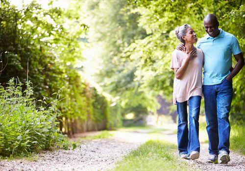 couple walking outside among greenery