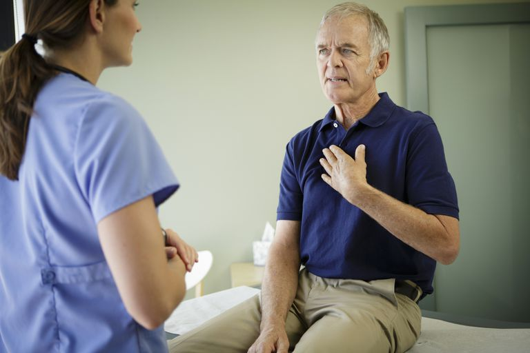 Man talking to nurse, holding chest