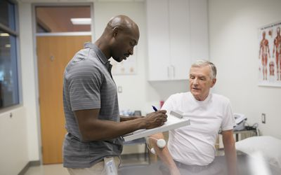 Physical therapist taking notes with patient examination room