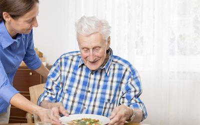 A woman helping an elderly man eat