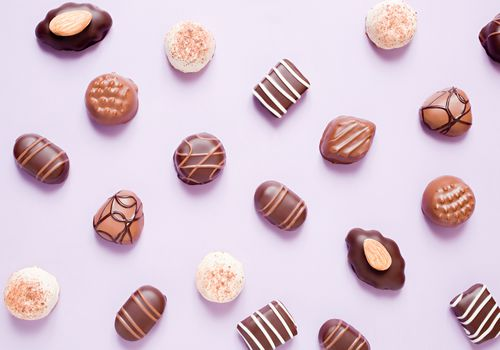 assorted chocolates on a light purple background