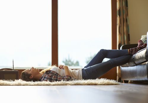 woman lying on carpet on floor with feet on couch