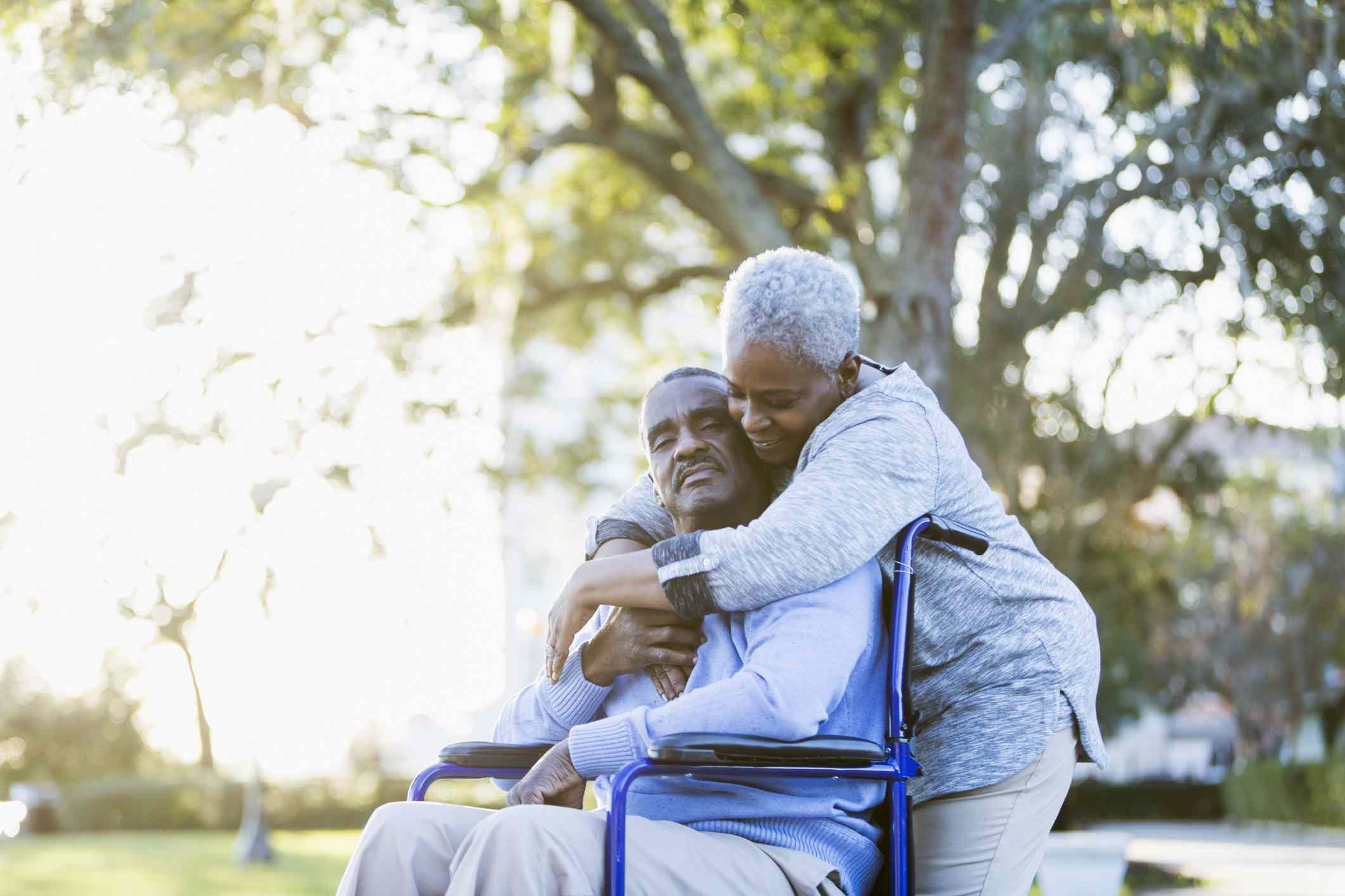 Senior man in wheelchair being hugged from behind by wife