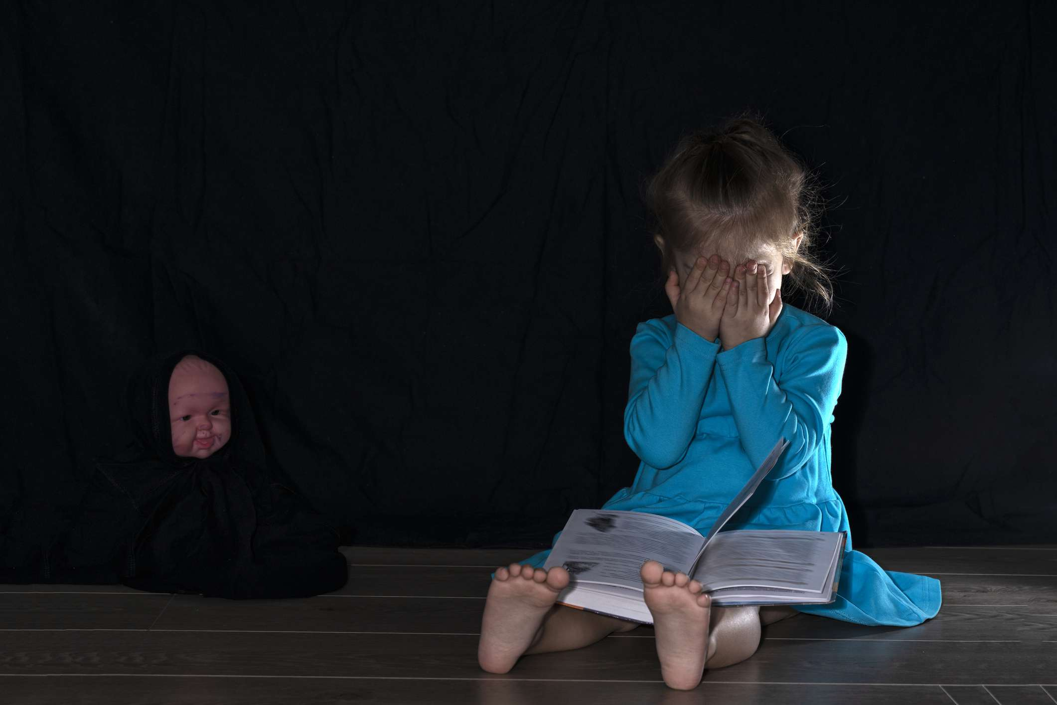 A child in a dark room sitting on the floor covers her eyes